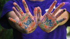 Due mani decorate da molte scritte colorate